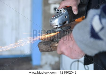Close Up Of A Man Sharpen An Ax Using Electric Grinder. Sparks While Grinding Iron. Selective Focus