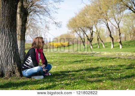 Thoughtful Brunette Sitting Under A Tree In A Park On A Sunny Day