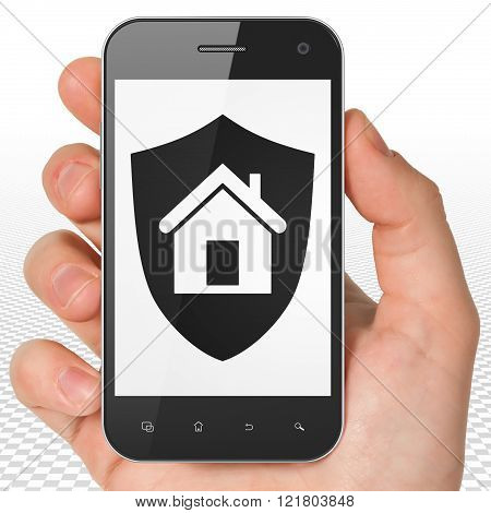 Finance concept: Hand Holding Smartphone with Shield on display