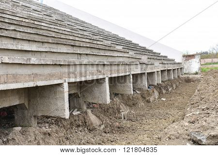 Old dirty destroyed grandstands at stadium under construction