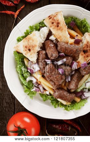 Cevapcici, bosnian minced meat kebab with french fries, onion and somun bread