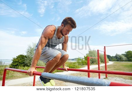 fitness, sport, exercising, training and lifestyle concept - young man doing abdominal exercise on parallel bars in summer park