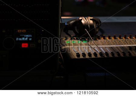 Blurry background of digital mixer and fader for music recording radio or tv broadcasting in dark light.