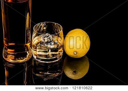 Bottle And A Glass Of Whiskey With Ice And  Lemon On A Black Background
