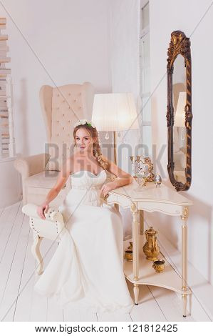 Beautiful bride blond girl in a wedding dress worn front of the mirror