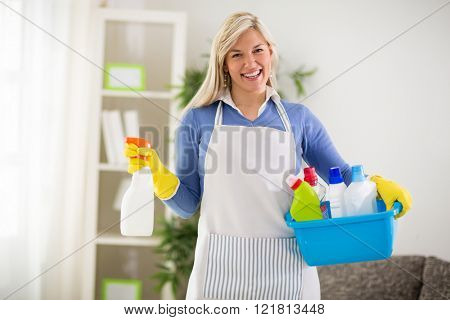 Smiling female wears cleaning products in plastic washbowl