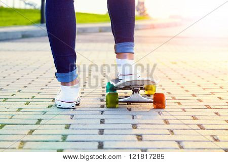 Skateboarder girl legs and board on sunse