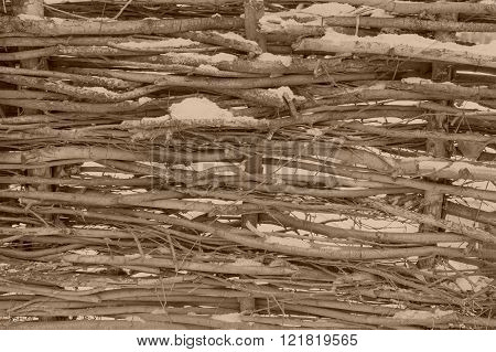 Snow-covered Wattle Fence From Wooden Branches Of Sepia Tone