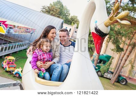 Father, mother, daughter enjoying fun fair ride, amusement park