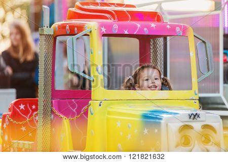 Little girl enjoying fun fair ride, amusement park