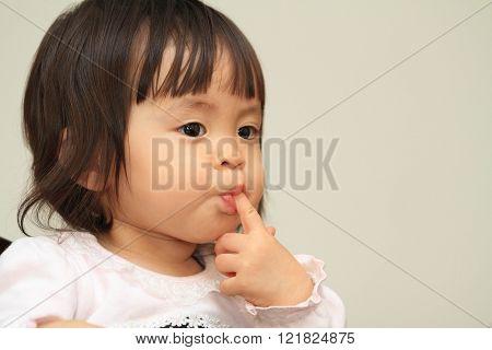 Japanese baby girl sucking her finger (1 year old)