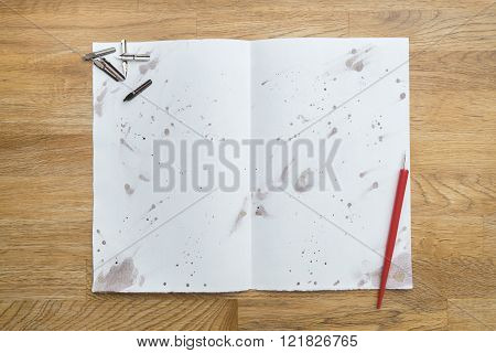 Blots Of Ink With A Pen On A White Paper On A Wooden Table