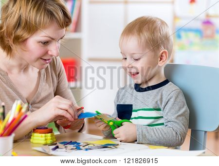 Woman teaches child handcraft at kindergarten or playschool or home