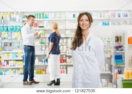 Chemist Smiling While Assistant And Customer Standing In Backgro