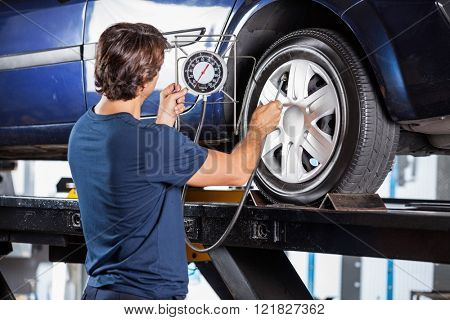 Mechanic Looking At Gauge While Inflating Car Tire