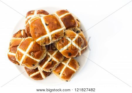 A plate full of freshly baked hot cross buns for the Easter holidays on an isolated white background.