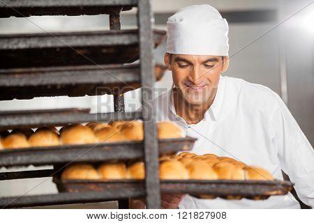 Smiling Baker Removing Baking Tray From Rack