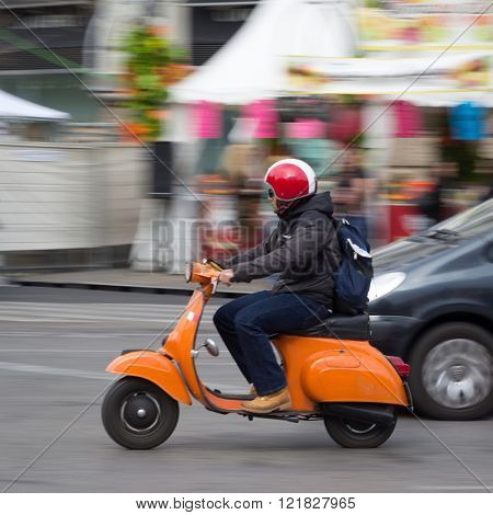 VALENCIA, SPAIN - MARCH 14, 2016: A man on a Vespa scooter traveling in the town center of Valencia with motion blur. Vespa is an Italian brand of scooter manufactured by Piaggio.