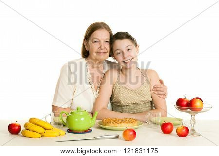 The Grandmother And The Granddaughter Sit At A Table