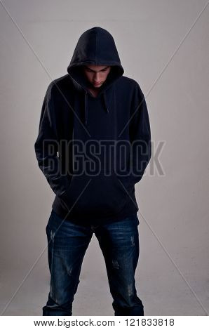 teenager with hoodie looking down against a dirty gray wall