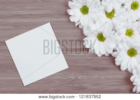 white flowers on wood background with notebook