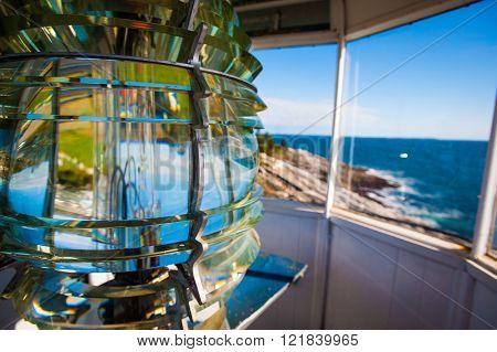 Beautiful colorful Lighthouse Fresnel lens along Atlantic Ocean coast in New England marking lighting rocky shore