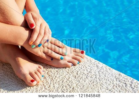 Vacation idea. Woman feet closeup. Beautiful pedicure. Girl relaxing beside swimming pool enjoying sun on sunny summer day.