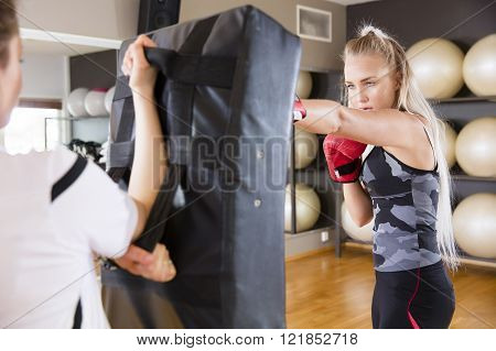 Two focused women boxing at the gym