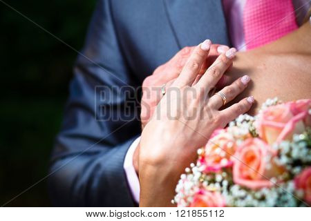 Hands with wedding ring on brides shoulder