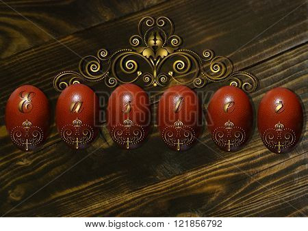 Easter eggs with a gold ornament on a dark wooden board