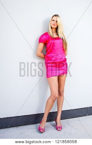 Blond young woman in pink dress posing near modern building