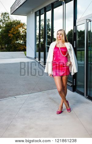 Blond young woman in pink dress and white coat posing