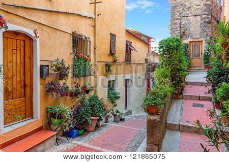 Narrow street among old houses in historic part of Menton - town on French Riviera.