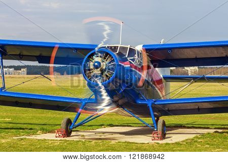 Airplane with the rotating propeller. Old retro blue plane close-up. Front view with the side of the fuselage.