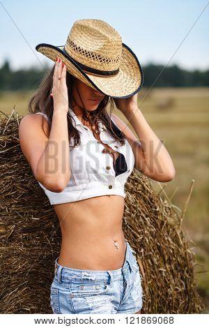 Girl holding cowboy hat.