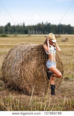 Woman in cowboy hat near a straw bale