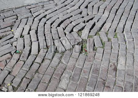 Bricks laid as street cobblestones. The pattern is disrupted by long use.