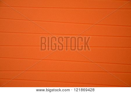 Orange rubber tablemat with grooves closeup - background