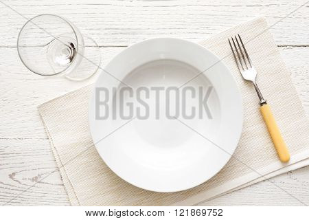 Empty White Round Soup Or Pasta Plate With Fork And Glass. On White Wood From Above.