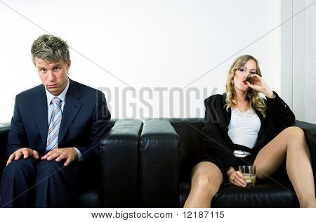 A bossy woman drinking and smoking, a uptight man – a metaphor for the battle of the sexes in professional life
