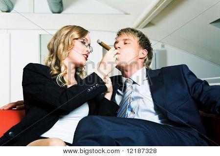 Secretary helps her boss smoke a cigar