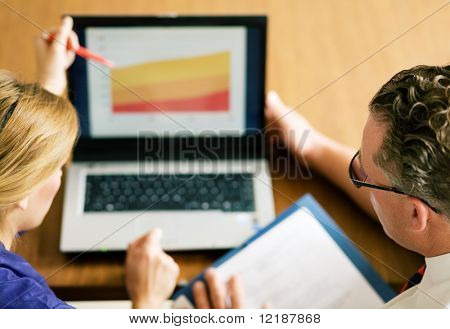 Two office workers (male / female) working on a presentation (very shallow depth of field, focus on glasses of the man)