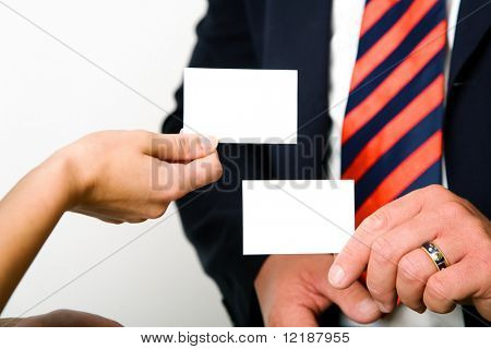 Businesspeople (male / female) exchanging their (blank) business cards (shallow depth of field)