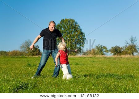 Dad an young daughter playing soccer in the grass