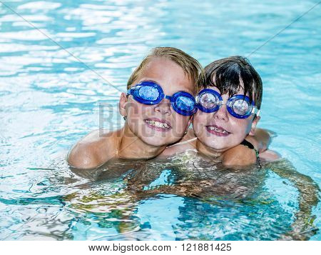 two funny boys wearing swimming goggles embracing each other