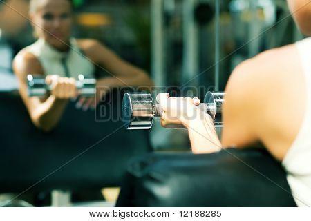 Frau Aufhebung Hanteln in ein Fitness-Studio, sehen sich in einem Spiegel (Schwerpunkt nur auf die Hantel)