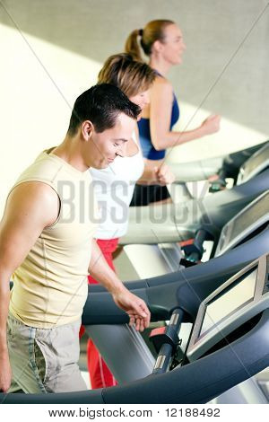 Three people on the treadmill in a gym running