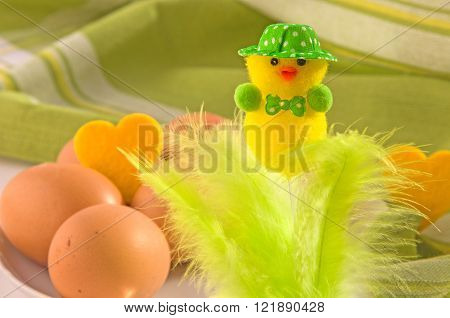 Easter decoration (cute neatly hatted chicken with bow tie) and eggs on cotton napkin. Main colors: yellow white green.