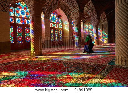 SHIRAZ, IRAN - March 01, 2016: Young Muslim woman praying in Nasir Al-Mulk Mosque (Pink Mosque), Iran, Shiraz
