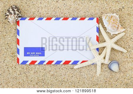Blank classic air mail envelope on the sand decorated with sea shells and Starfish